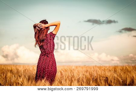 Style Redhead Girl In Red Dress Tay On Yellow Wheat Field In Sunset Time And Looking Forward. Image