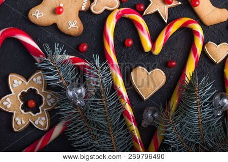New Year And Christmas Background. Christmas Candy Cane Gingerbread  Fir Tree Branches On The Black