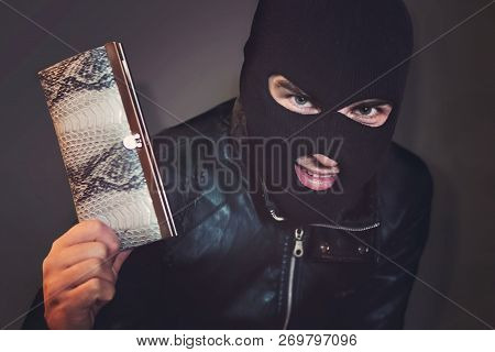 Masked Criminal At The Black Background Grins Looking At The Viewer And Showing A Purse In Hand. Evi