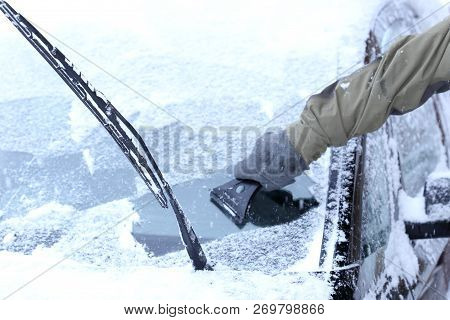 a man is scraping the windshield in winter poster