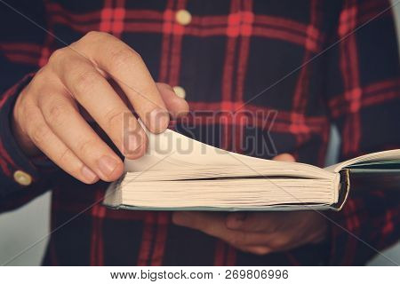Close Up Of A Young Male In A Chequered Shirt Holding The Book And Turning Over The Page. Ingusitive