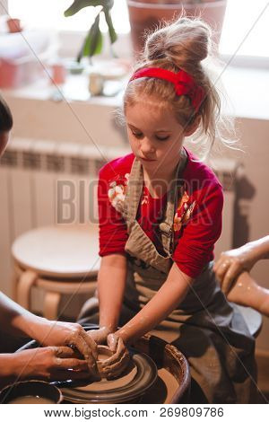 Young Seven Years Old Girl In Pottery Workshop Creating A Bowl From Clay. Pottery Workshop For Kids