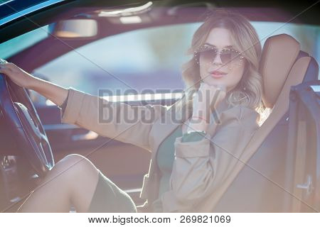 Photo Of Happy Blonde With Glasses And Long Dress Sitting In Car With Open Door In Afternoon. Lensfl