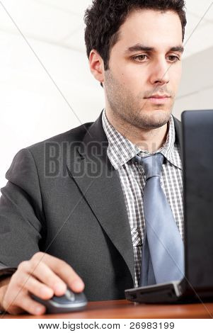 A portrait of a young handsome businessman being thoughtful looking at his laptop