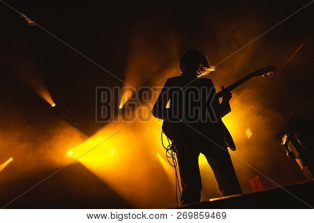 Guitarist Plays Solo. Silhouette Of Guitar Player In Action On Music Stage. Popular Music Rock Band