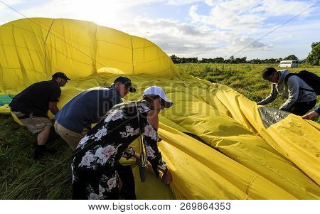 Gold Coast, Australia - November 14, 2018:  Passengers Of The Hot Air Balloon Helping Folding Up The