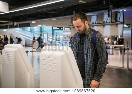 Handsome Young Bearded Man Doing Self Check-in At Airline Check In Counter Machine