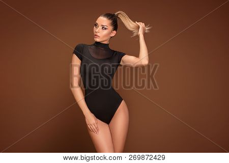 Sensual Woman Posing On Brown Background.