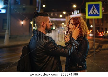 Couple In Love On Date. Boyfriend Strokes Girlfriend Hair. She Smokes An Electronic Cigarette. They