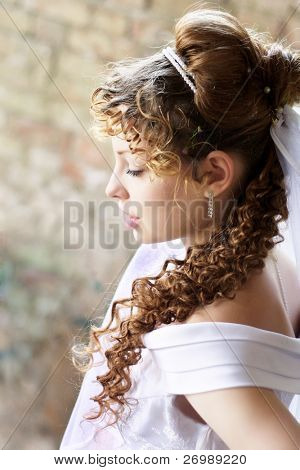 Picture of beautiful curly bride against the backdrop of the stone ruins