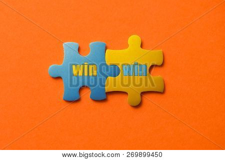 Two Colored Details Of Puzzle With Text Win Win On Orange Background, Yellow And Blue, Close Up.