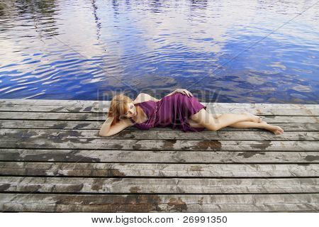 Images of a beautiful red-haired girl on the pier in a purple dress