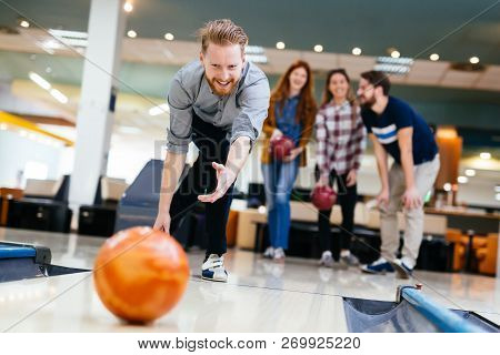 Cheerful Friends Bowling Together And Having Fun