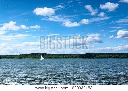 Yacht, Sailing On The Lake, Behind The Shore, Covered With Forest. Sunny Day, Blue Sky With Clouds,