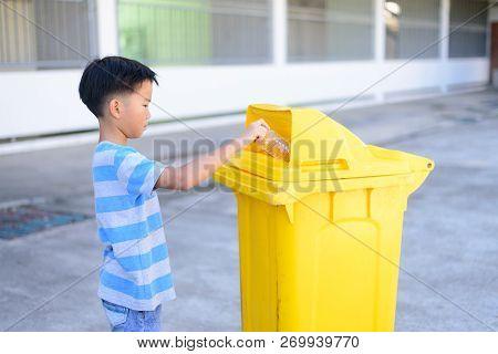 Young Boy Hand Trow Plastic Bottle In A Yellow Bin