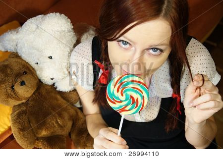 Red head girl with lollipop and teddy bears
