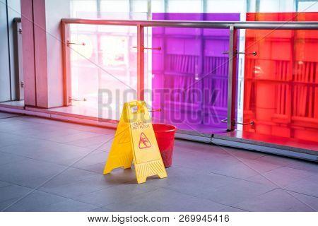 Yellow Caution wet floor sign on wet floor with red bucket