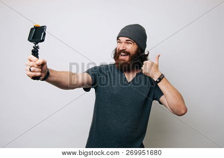 Cheerful Young Bearded Man Showing Thumb Up And Taking A Selfie With His Smartphone With Selfie Stic