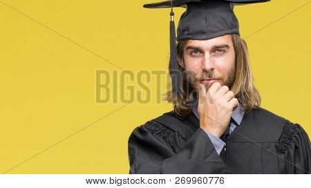 Young handsome graduated man with long hair over isolated background looking confident at the camera with smile with crossed arms and hand raised on chin. Thinking positive.