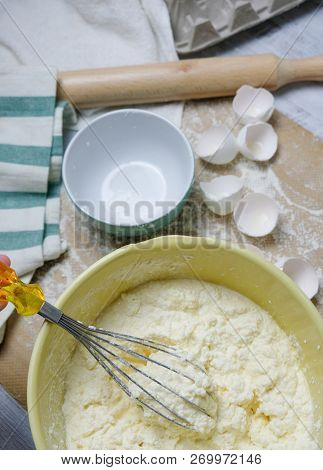 Cooking Process Of Homebaked Cottage Cheese Pie. Raw Ingredients In Bowl, Table With Kitchen Objects
