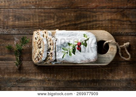 high angle view of a stollen cake for christmas time sprinkled with icing sugar, placed on a wooden rustic table