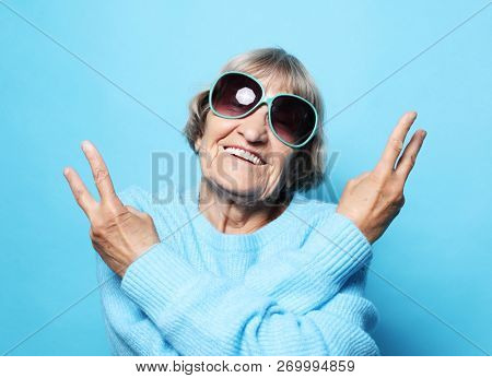 Lifestyle, emotion  and people concept: Funny old lady wearing blue sweater, hat and sunglasses showing victory sign. Isolated on blue background.