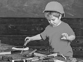 Kid boy holds screwdriver tool. Handcrafting and workshop concept. Child in helmet cute playing as builder or repairer, or handcrafting. Toddler on busy face plays with screwdriver at workshop poster
