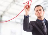 Businessman drawing a rising arrow, representing business growth. poster