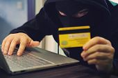 Man in robber mask uses internet, bank account and credit facilities. Phishing attack by male with hidden face. Hacker enters stolen financial data. Confidential information was taken by fraudster. poster
