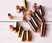 Nine 40 caliber hollow point bullets and eight 44 special bullets with red tips shown on a wooden background, shot from above poster
