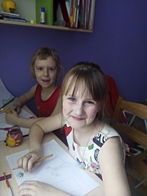 Two Girls With Bangs Draw At The Table And Smile. Two Blonde First-class Students Do Their Homework.