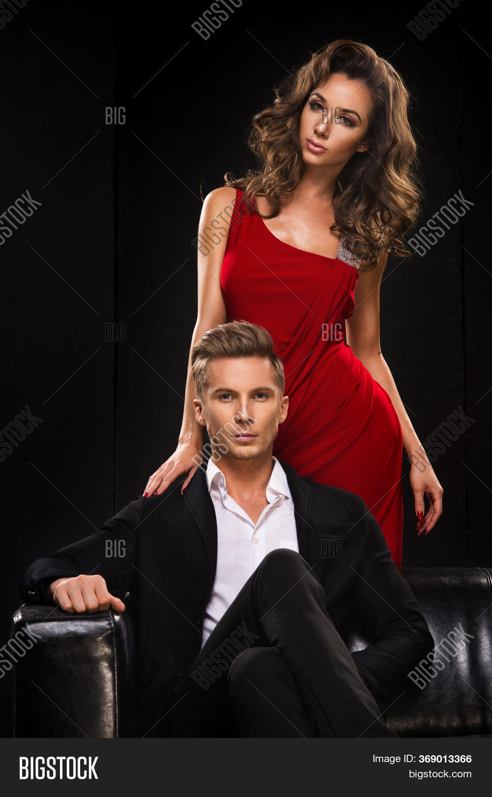 Elegant Couple. Woman In Red Dress And Man In Black Suit