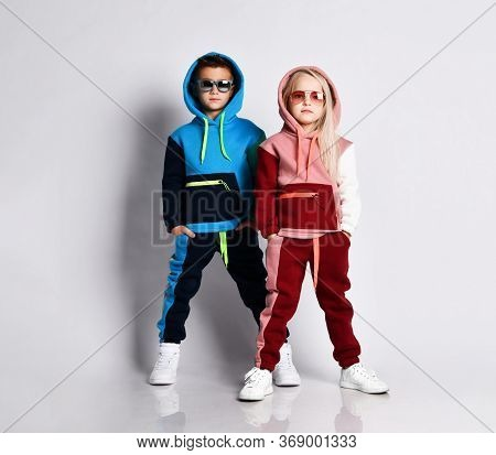 Little Kids, Boy And Girl, In Sunglasses And Hoods, Colorful Tracksuits, Sneakers. They Posing Isola
