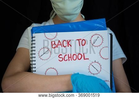 Close-up Of Student Wearing Face Mask And Surgical Gloves, Holding School Books With Back To School