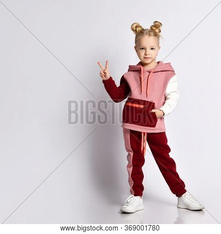 Pretty Smiling Girl In A Fashionable Sports Suit With A Stylish Hairstyle, Posing With The Victoria