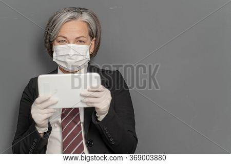Gray-haired Businesswoman Works Notepad. Caucasian Lady Holds Tablet Looking At Camera On Gray Backg