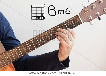 Learn Guitar - Man In A Dark Blue Shirt Playing Guitar Chords Displayed On Whiteboard, Chord B Minor