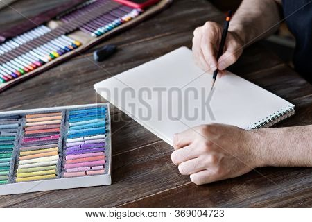 Man Painting With Color Pencil And Pastel Crayon Chalks On Paper. Box Of Pastel Chalks And Color Pen
