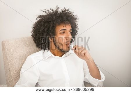 Young Businessman Smoking Of Electronic Cigarette Looking At Side With Textspace Or Copy Cpase. Hand