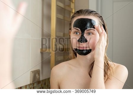 A Woman With A Cleansing Black Mask On Her Face In Her Bathroom