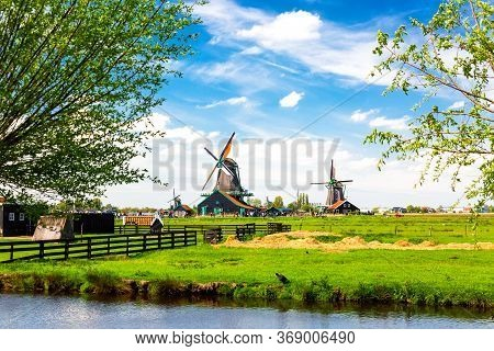 Dutch Typical Landscape. Traditional Old Dutch Windmills With Blue Cloudy Sky In The Zaanse Schans V