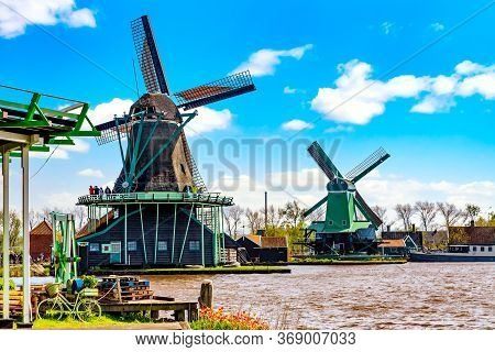 Typical Iconic Landscape In The Netherlands, Europe. Traditional Windmills In Zaanse Schans Village