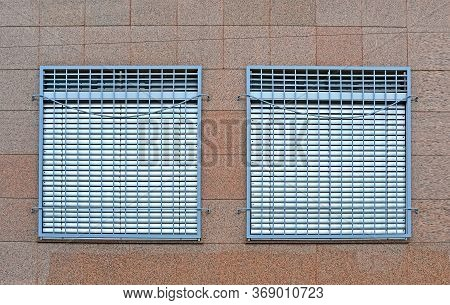 few metal windows grid with jalousie aka blinds on red stone granite wall