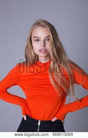 Nice Portrait Of Well-dressed Fashionable Girl In Orange Sweatshirt. Lovely Lady Posing Indoors On G