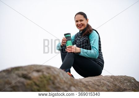 Happy Beautiful Woman Resting on the Rock after Running Outdoor. Workout at Autumn Evening. Sport and Healthy Active Lifesyle.