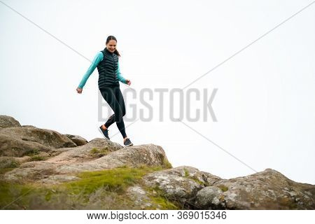 Beautiful Woman Running on the Mountain Trail at Cold Autumn Evening. Sport and Active Lifestyle Concept.