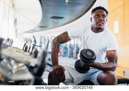Young African American Man Sitting And Lifting A Dumbbell Close To The Rack At Gym. Male Weight Trai