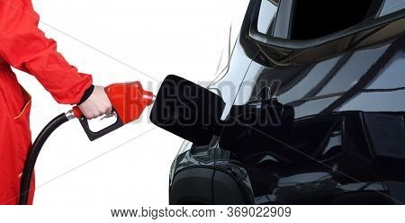 Man hand is holding red gasoline pistol pump fuel nozzle on gas station