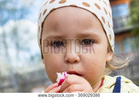 Close Up Portrait Of A Child With A Piercing Gaze Eating A Healthy Vegetable. Little Hungry Child Ea