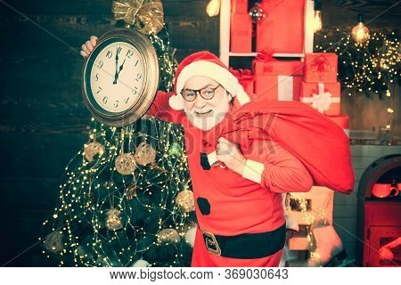Cheerful Santa Claus Holding Alarm Clock On Fireplace And Christmas Tree Background. Santa Claus At